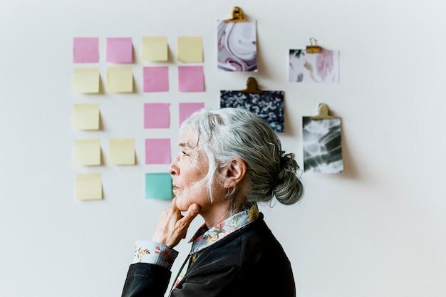Senior businesswoman brainstorming des idées sur un mur