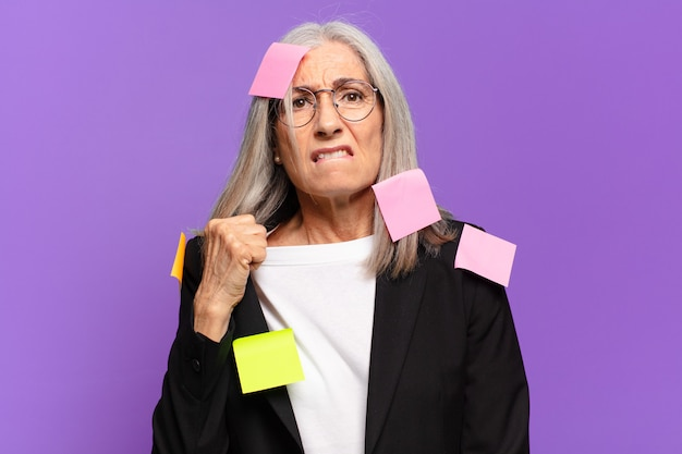 Senior businesswoman avec poteau adhésif. concept d'entreprise humoristique