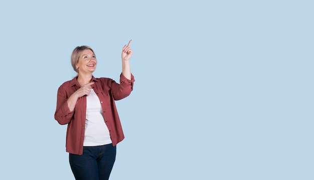 Senior caucasian woman avec des cheveux blonds pointant vers l'espace libre bleu près d'elle avec l'index