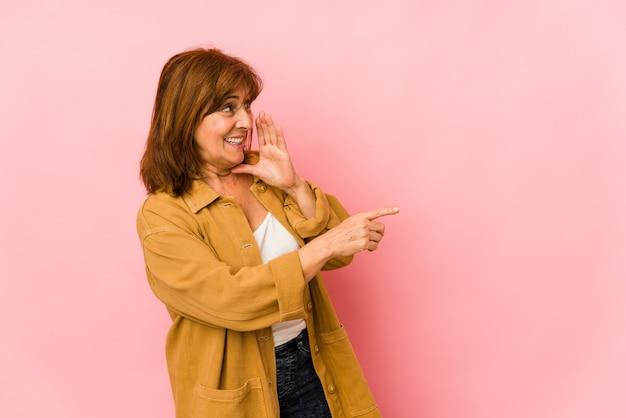 Senior caucasian woman isolated disant un ragot, pointant vers le côté rapportant quelque chose.