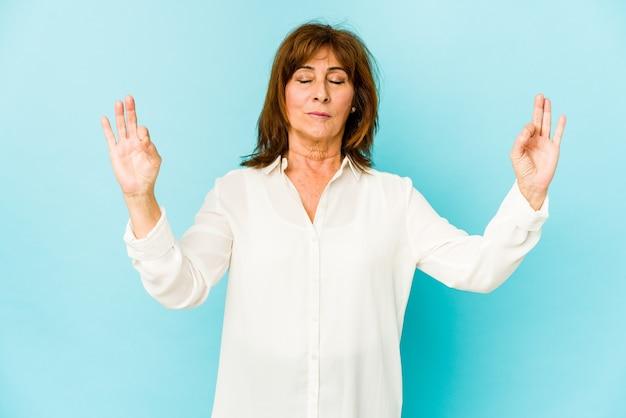 Senior caucasian woman isolated se détend après une dure journée de travail, elle effectue du yoga.