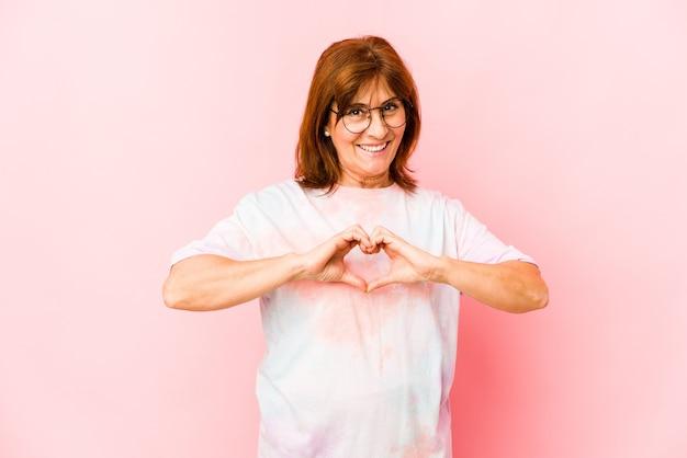 Senior caucasian woman isolated smiling et montrant une forme de coeur avec les mains.
