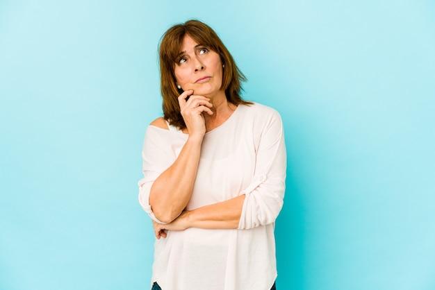 Senior caucasian woman isolé en contemplant, en planifiant une stratégie, en réfléchissant à la manière d'une entreprise