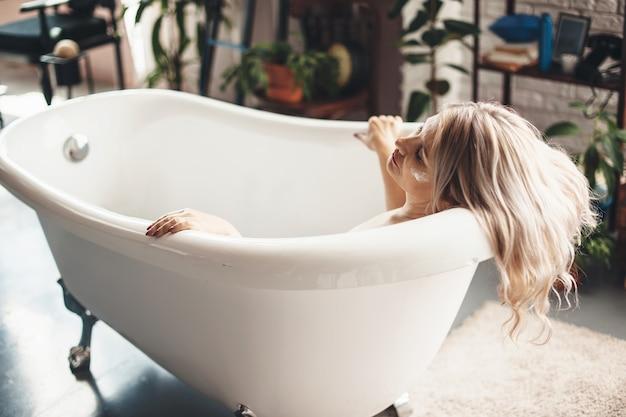 Senior caucasian woman posing dans une baignoire avec une crème anti-vieillissement sur le visage