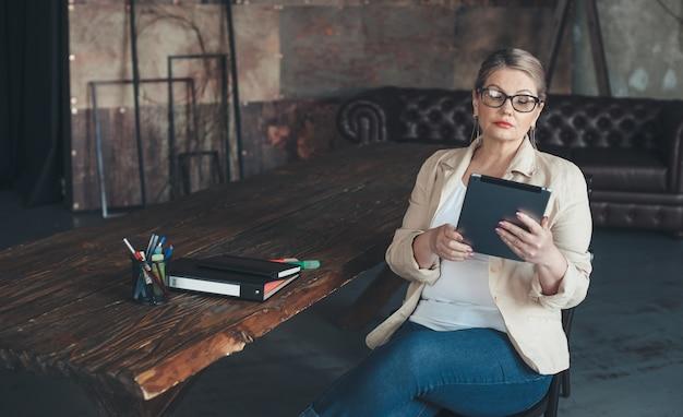 Senior caucasian woman travaillant sur un projet à l'aide d'une tablette et de dossiers à la maison à distance