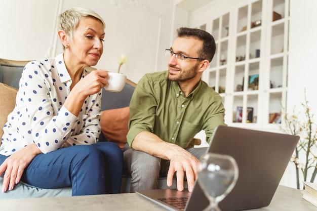 Senior caucasian woman with a cup regardant l'écran de l'ordinateur pendant la séance d'astrologie