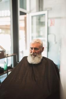 Senior client mâle avec cape dans le salon de coiffure