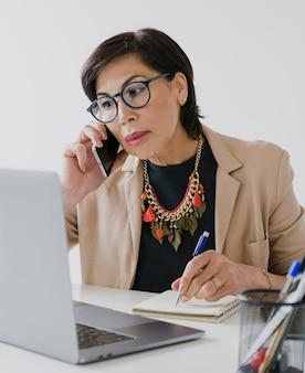 Senior avec collier parlant au téléphone sur son bureau
