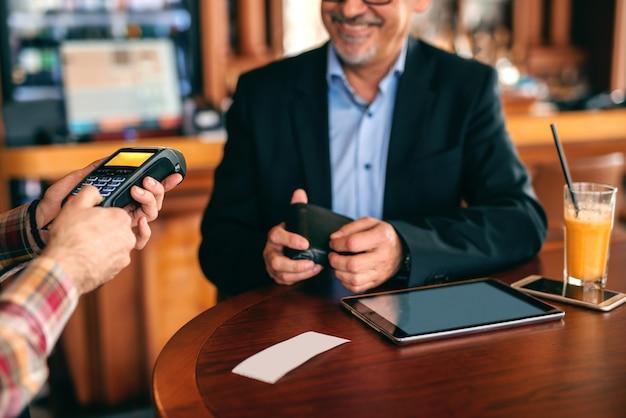 Senior en costume payant la facture par carte de crédit tout en étant assis dans la cafétéria.