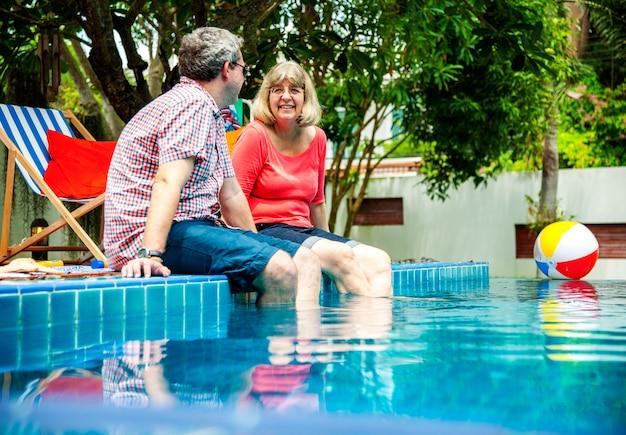 Senior couple adulte, appréciant l'heure d'été à la piscine ensemble