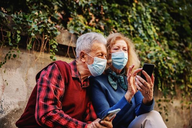 Senior couple amoureux portant des masques chirurgicaux de protection et regardant un téléphone intelligent