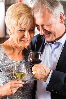 Senior couple au bar avec verre de vin à la main