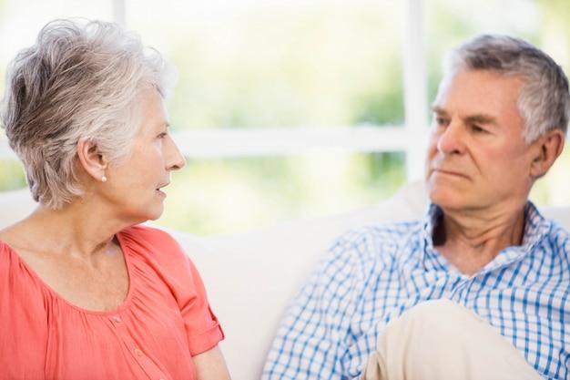 Senior couple ayant une dispute sur le canapé à la maison
