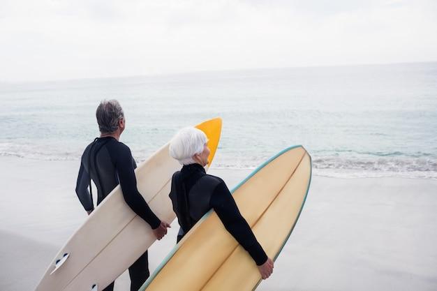 Senior couple en combinaison de surf tenant la planche de surf sur la plage