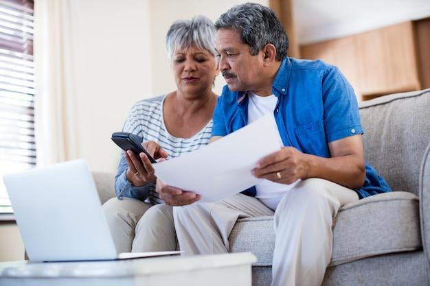 Senior couple contrôle des factures dans la salle de séjour