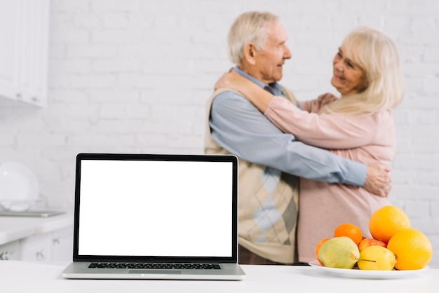 Senior couple dansant derrière un ordinateur portable dans la cuisine