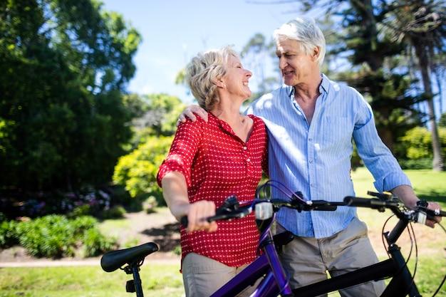 Senior couple debout avec vélo dans le parc