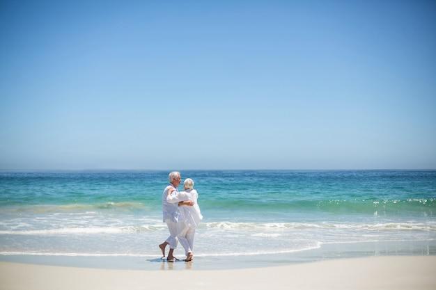 Senior couple embrassant à la plage