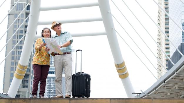 Senior couple est assis tenant la carte pour rechercher des destinations dans les rues.