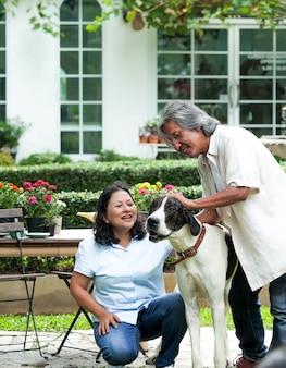 Senior couple jouant avec gros chien dans le jardin de la maison.