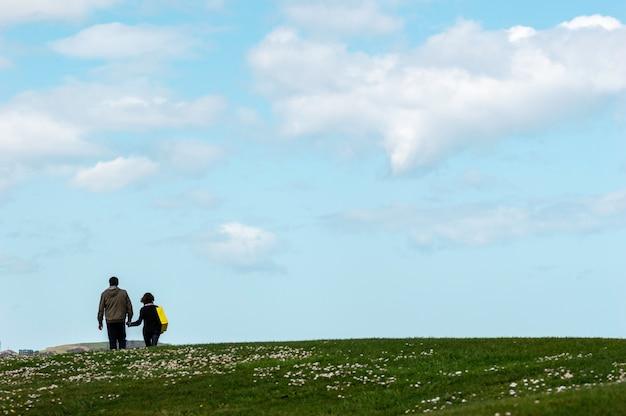Senior couple marchant joyeusement dans le parc avec un ciel bleu en arrière-plan.