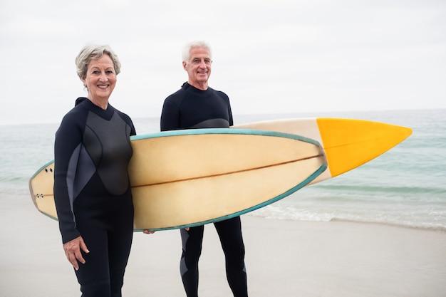 Senior couple avec planche de surf debout sur la plage