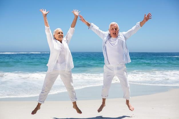 Senior couple sautant avec les bras levés