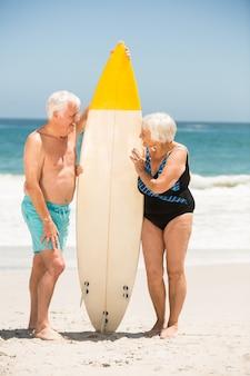Senior couple tenant une planche de surf