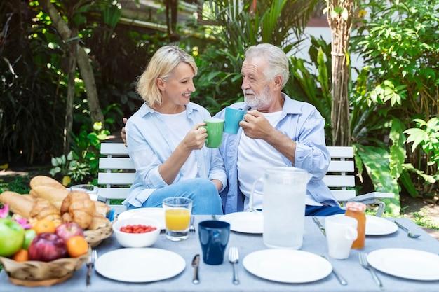 Senior couple en train de déjeuner dans le jardin avec heureux