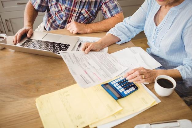 Senior couple vérifiant leurs factures à la maison