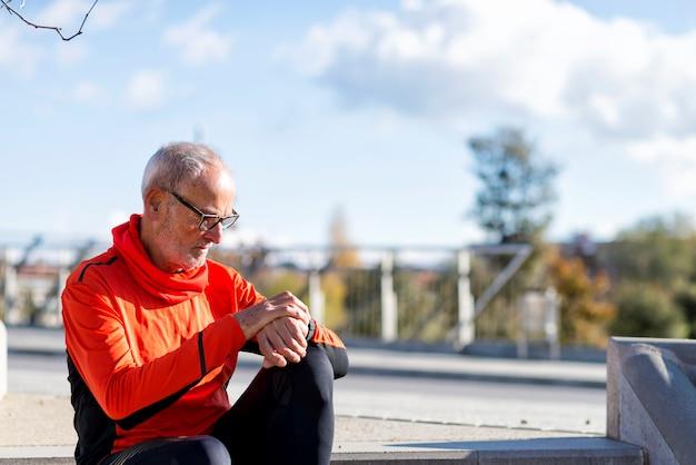 Senior coureur homme assis et regardant smartwatch pendant l'entraînement. il est satisfait des résultats.