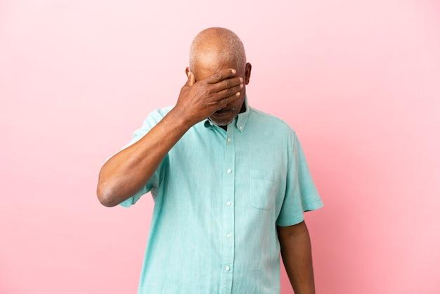Senior cubain isolé sur fond rose couvrant les yeux à la main. je ne veux pas voir quelque chose