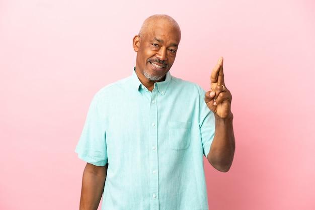 Senior cubain isolé sur fond rose avec les doigts croisés et souhaitant le meilleur