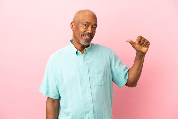 Senior cubain isolé sur fond rose fier et satisfait de lui-même