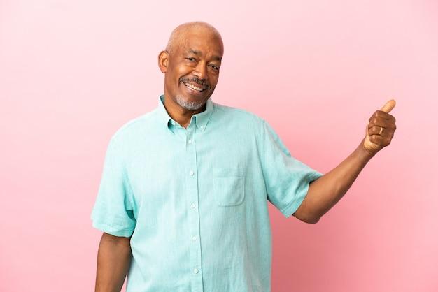 Senior cubain isolé sur fond rose pointant sur le côté pour présenter un produit