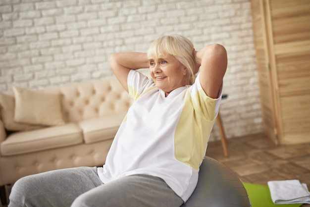 Senior dame faisant des exercices de presse sur fitness ball.