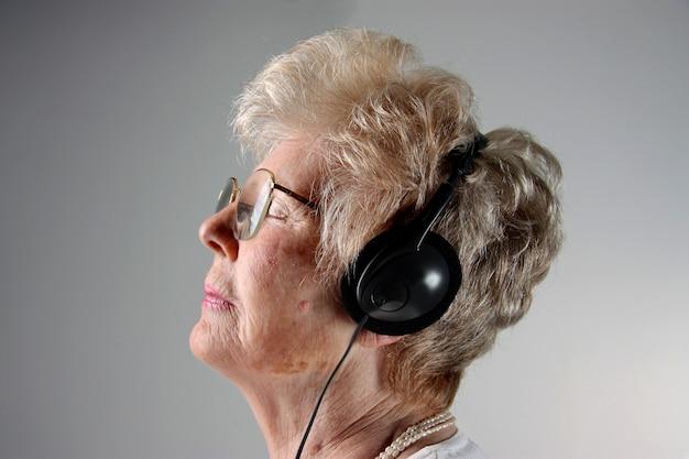 Senior dame sur le profil avec des écouteurs