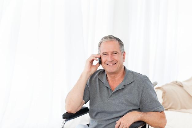 Senior dans son fauteuil roulant téléphonant