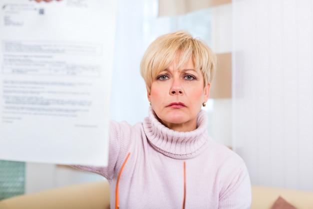 Senior à domicile recevant une lettre négative