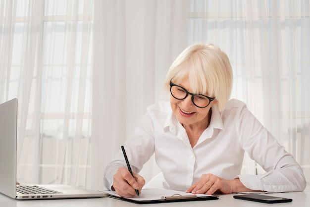 Senior écrit sur un presse-papiers