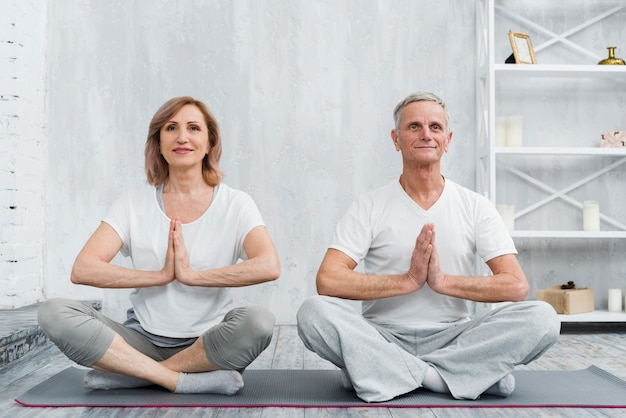 Senior famille couple assis en posture de lotus sur tapis d'yoga gris