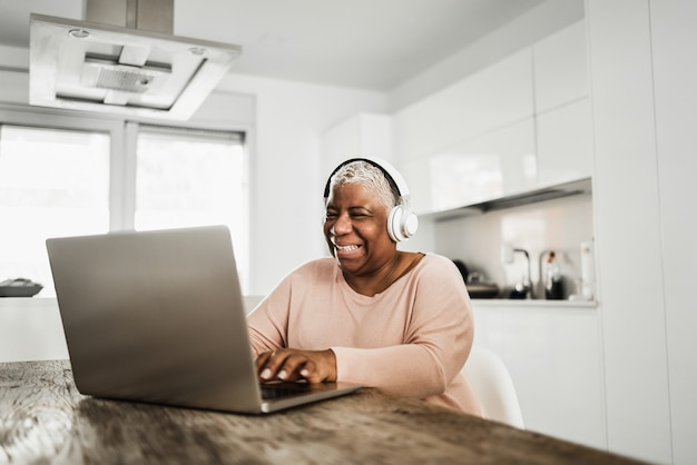 Senior femme africaine à l'aide d'un ordinateur portable tout en portant des écouteurs à la maison - focus sur le visage