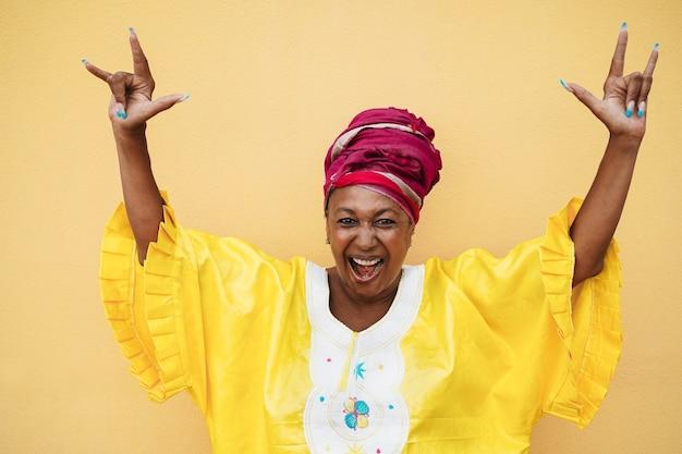 Senior femme africaine danse en plein air - focus sur le visage