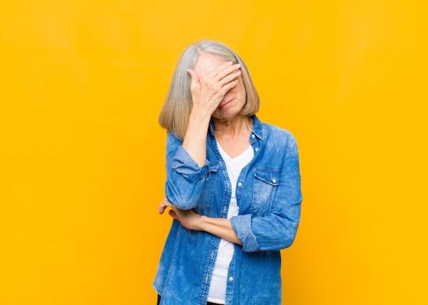 Senior ou femme d'âge moyen à stressé, honteux ou bouleversé, avec un mal de tête, couvrant le visage avec la main