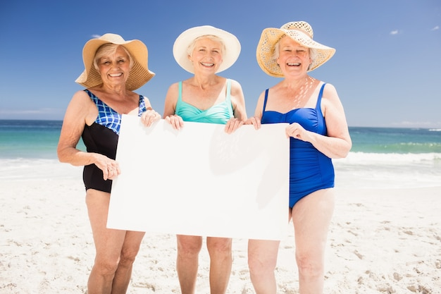 Senior femme amis tenant un papier vierge