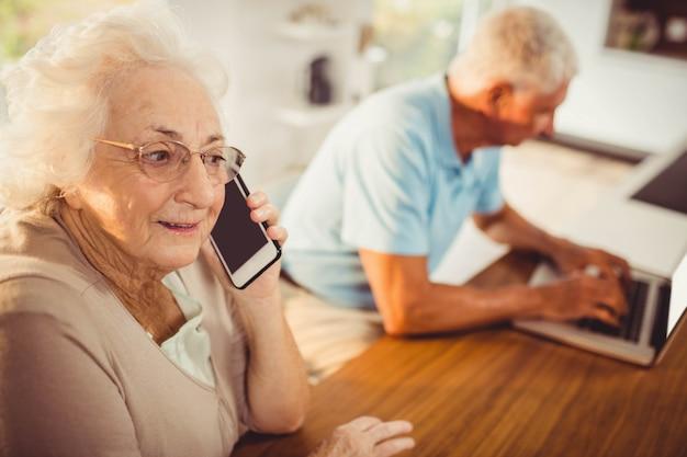 Senior femme sur un appel téléphonique à la maison