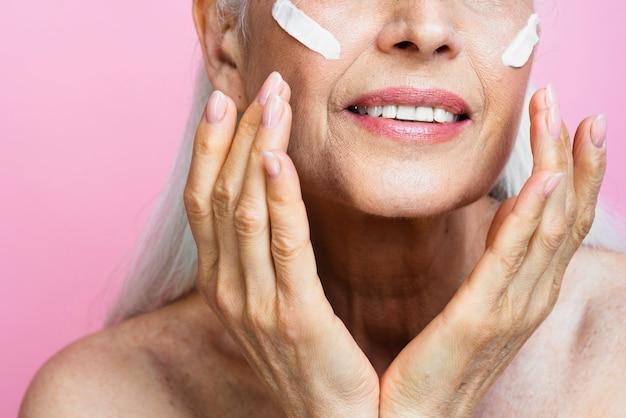 Senior femme appliquant des soins de la peau sur le visage