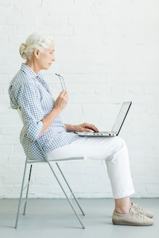 Senior femme assise sur une chaise à l'aide d'un ordinateur portable