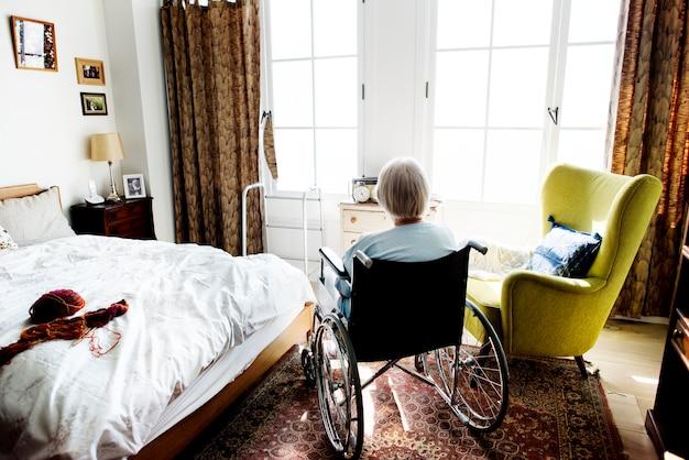 Senior femme assise seule sur le fauteuil roulant