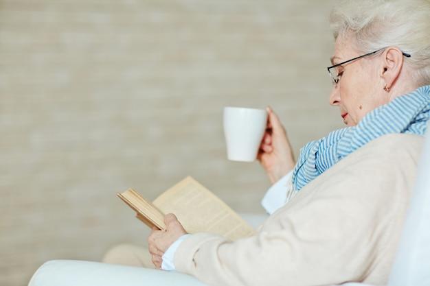 Senior femme aux cheveux gris avec livre passionnant